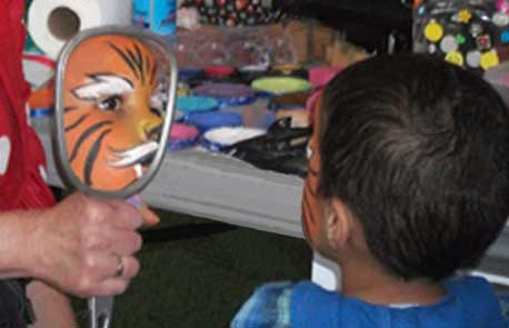 Photo of a boy awed by his tiger face-paint